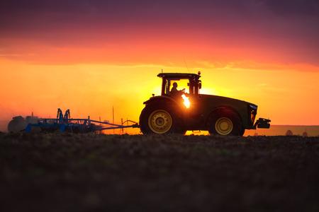 Farmer en tractor de preparación de la tierra con vibrocultivador, puesta del sol tiró Foto de archivo
