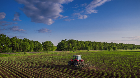 plough land: Tractor cultivating field at spring,aerial view