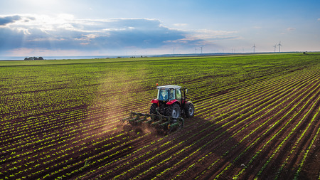 Tractor cultivating field at spring,aerial view Stock Photo