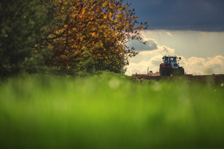 plough land: Farmer in tractor preparing land with seedbed cultivator