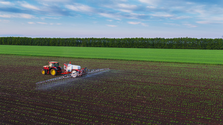 Tractor de fumigación de campo en la primavera, vista aérea