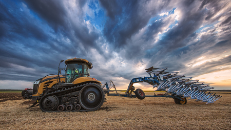 plough: Farmer in Tractor with Plough, Plowing in a Field Stock Photo