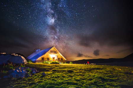Hut in the mountains at night under the stars