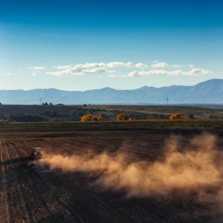 Tractor cultivating field at autumn ,aerial view 版權商用圖片