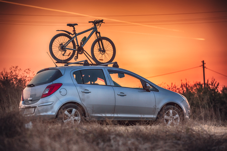 rack mount: Car is transporting bicycle on the roof.
