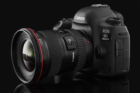 eos: Varna, Bulgaria - September 24, 2016: Canon 5D Mark IV camera with Canon EF 16-35mm f2.8L II USM lens on a black background. Canon is the world largest SLR camera manufacturer. Editorial