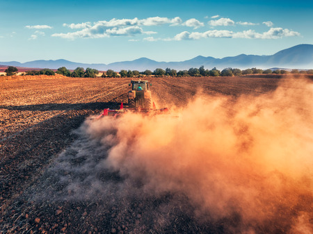 arando: Tractor cultivando campo en el otoño, vista aérea