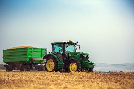deere: Varna Region, Bulgaria - June 20, 2015: A modern John Deere 6115R tractor with the trailer on a yellow field.The 6115R has Premium ComfortView cab.Full Frame design, 2.580 m wheelbase and 4.5 l DieselOnly PowerTech PVX engine