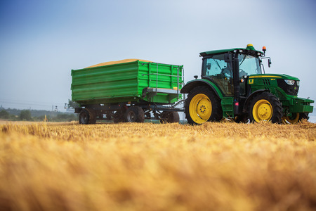 Varna Region, Bulgaria - June 20, 2015: A modern John Deere 6115R tractor with the trailer on a yellow field.The 6115R has Premium ComfortView cab.Full Frame design, 2.580 m wheelbase and 4.5 l DieselOnly PowerTech PVX engine