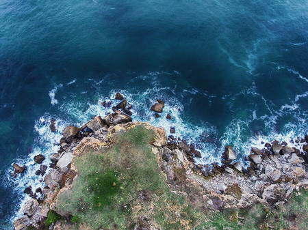 Aerial view of rocky coastline with crop fields and crashing ocean waves