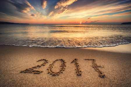 extreme weather: Happy New Year 2017 concept written on the sea beach at sunrise Stock Photo