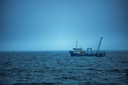 Trawler fishing boat sailing in open waters on a cold and foggy morning, sunrise