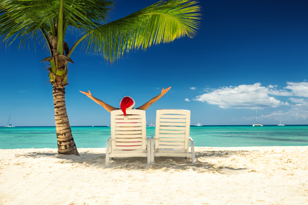 Woman in santa's hat  relaxing on tropical beach photo