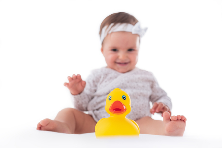 yellow teeth: Cute baby girl playing with yellow rubber duck isolated on white background