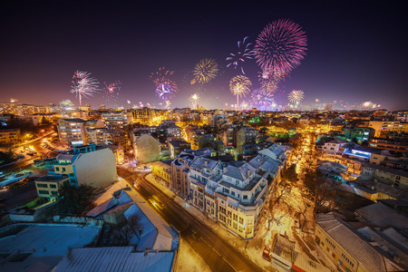 Downtown Varna cityscape with many flashing fireworks celebrating New Years Eve
