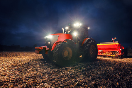 Tractor preparing land with seedbed cultivator at night Standard-Bild