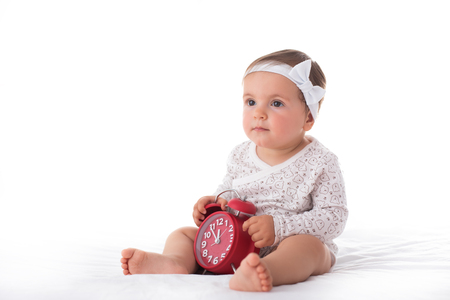 Adorable baby girl portrait with alarm clock isolated on white background Stock Photo