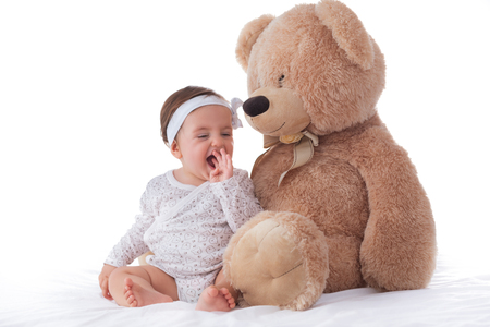 Happy baby girl playing with fluffy teddy bear isolated on white background