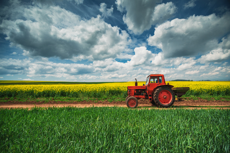 plowing: Red tractor in a field and dramatic clouds