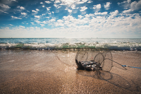 Fishing net coop trap , a floating basket for keeping live fish in water.