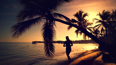 Sea sunrise. Woman running on the tropical island beach Punta Cana, Dominican Republic photo
