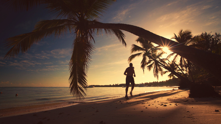 Sea sunrise. Man runing on the tropical island beach Punta Cana. photo