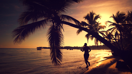 Beautiful sea sunrise. Young woman running on the tropical island beach  Punta Cana, Dominican Republic photo