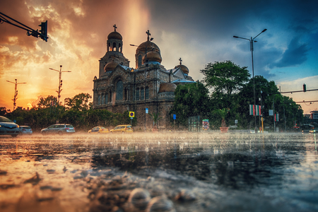 The Cathedral of the Assumption in the city centre of Varna and street traffic. Summer rain.