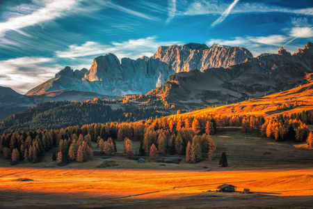 Paesaggio aereo di alba di autunno con i larici gialli e la piccola costruzione alpina e il gruppo della montagna di Odle - Geisler su fondo. Alpe di Siusi (Alpe di Siusi), Alpi dolomitiche, Italia. Archivio Fotografico