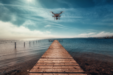 Beautiful morning over the sea. Pier on the foreground and flying drone. 스톡 콘텐츠