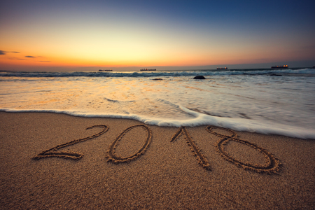 Happy New Year 2018 concept, lettering on the beach. Sea sunrise. Reklamní fotografie - 90173354