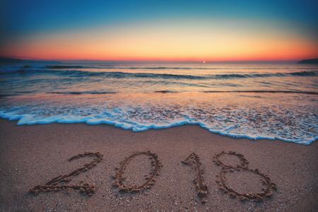 Felice anno nuovo 2018 concetto, scritte sulla spiaggia. Alba del mare