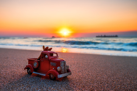 Sunrise on tropical island beach and car truck miniature. Stock Photo