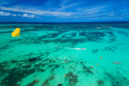 Aerial drone view of people enjoying water sports sea activities for sport, fun, leisure or recreational pursuit near Punta Cana beach.