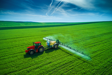 Aerial view of farming tractor plowing and spraying on field.