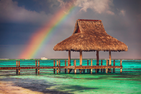 Rainbow over the  Wooden Water Villa  in Cap Cana, Dominican Republic. Фото со стока - 105478785