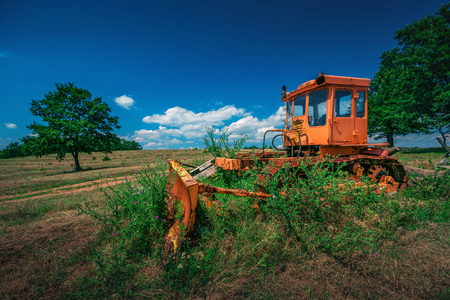 The bulldozer stayed in the field after work.