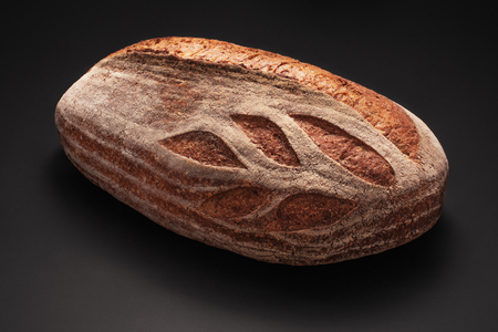Whole wheat sourdough freshly baked bread on black background. Archivio Fotografico
