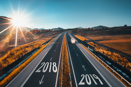Driving on open road at beautiful sunny day to new year 2018. Aerial view