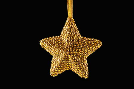 Golden Christmas star decoration on ribbon isolated on black background Stock Photo