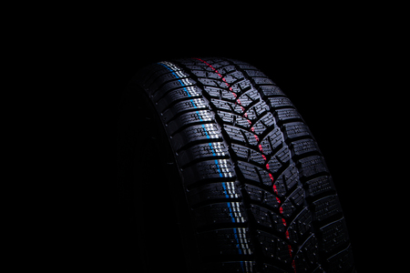 Winter Car tires on black background.