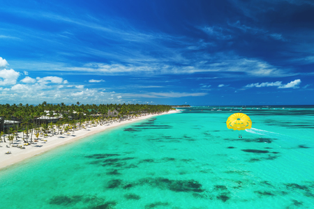 Tropical vacation in Punta Cana, Dominican Republic. Aerial view over beach resort. Parasailing. Sunbathing.