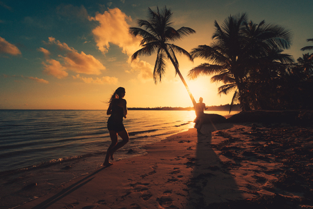 Sea sunrise. Woman running on the tropical island beach Punta Cana, Dominican Republic Reklamní fotografie