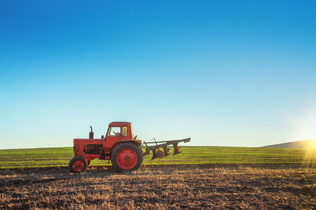 Tractor cultivating field at spring.