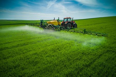Vue aérienne du tracteur agricole labourant et pulvérisant sur le terrain.