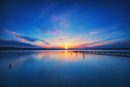 Small Dock and Boat at the lake, sunset shot Stock Photo