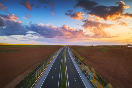 Aerial view of highway on sunset. Transportation background. Landscape with road near countryside fields.