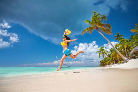 Carefree young woman relaxing on tropical beach. Imagens