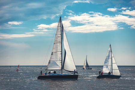 Żaglowiec jacht z białymi żaglami na morzu.
