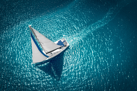 Regatta sailing ship yachts with white sails at opened sea. Aerial view of sailboat in windy condition.